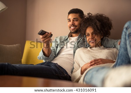 Cropped shot of a young african american couple watching television at home - stock photo
