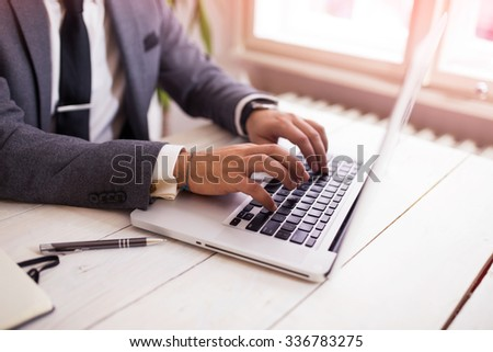 Cropped shot of a young man working from office using notebook computer, man's hands, man at his workplace using technology, flare light - stock photo
