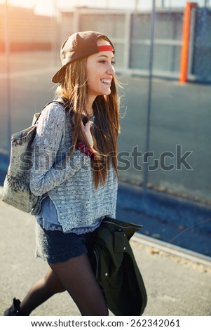 Cropped shot of a young stylish teenager walking in the street looking into the distance and feeling so happy,beautiful young female walk on a street relaxing and enjoying sunny evening outdoors,flare - stock photo