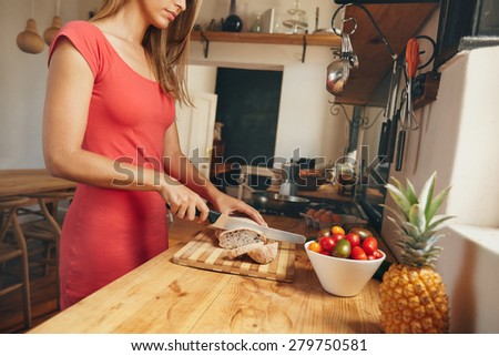 Cropped shot of a young woman slicing a fresh baked loaf of bread on a domestic kitchen counter. Female making morning breakfast. - stock photo