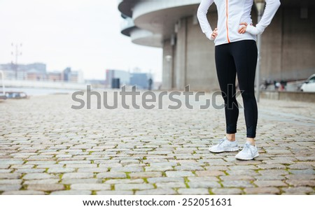 Cropped shot of a young woman standing on urban street while out for a run in the city. Fitness female standing with her hands on hips at sidewalk. - stock photo