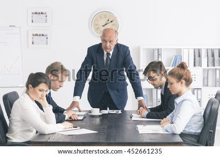 Cropped shot of an unhappy senior boss standing next to the table in the office - stock photo