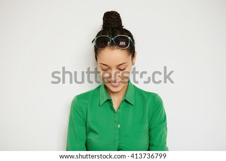 Cropped shot of brunette female model wearing green shirt looking and smiling down while posing against white studio wall. Portrait of young woman office worker enjoying free time at home at weekends - stock photo