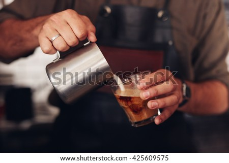 Cropped shot of coffee being prepared by a barista. Focus on hands holding cup of coffee and milk jar.