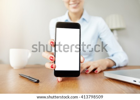 Cropped shot of cute smiling female office worker in white shirt showing funny pictures on cell phone with blank copy space screen for your text or advertising content. Selective focus, film effect - stock photo