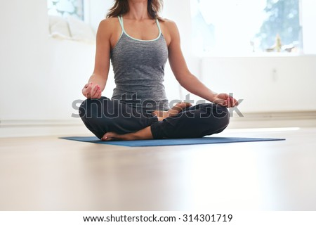 Cropped shot of fit female sitting cross legged on exercise mat with hands on knees meditating. Woman in lotus pose at health club. Padmasana, meditation posture. - stock photo