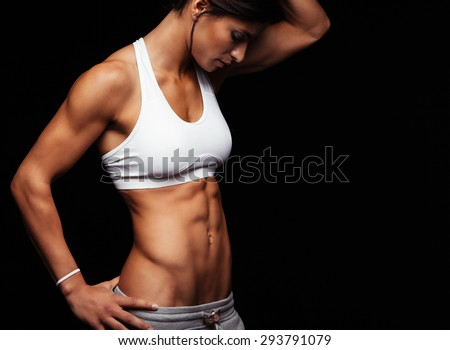 Cropped shot of fit woman's torso with her hands on hips. Female with perfect abdomen muscles posing on black background. - stock photo