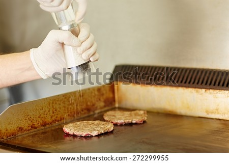 Cropped shot of gloved cook's hands grinding salt onto two hamburger patties to season them while they are frying on the grill   - stock photo