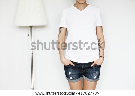 Cropped shot of hipster teenage girl wearing blank white T-shirt with copy space for your promotional content. Young Caucasian model posing indoor against home interior background. Lifestyle concept  - stock photo