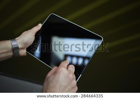 Cropped shot of male person holding digital tablet with beautiful reflection on the screen, business man connecting to wireless device, university student guy browsing internet via touch pad - stock photo