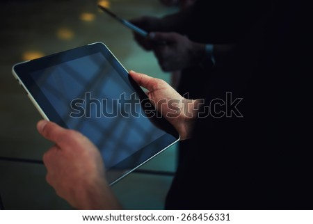 Cropped shot of male person using a digital tablet, man's hand typing text message zooming digital image on touchpad, businessman using his wireless devices during a meeting, work on a tablet screen