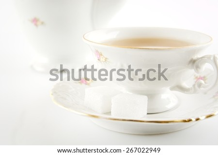 Cropped shot of old-style porcelain jug with a cup of tea on white background - stock photo