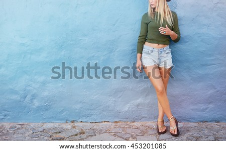 Cropped shot of stylish female model standing against blue wall. Young caucasian woman with copy space. - stock photo