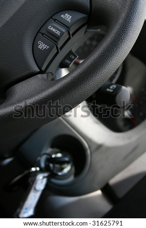 Cropped shot of the controls in a modern car, cruise control, steering wheel, key in ignition and more - stock photo