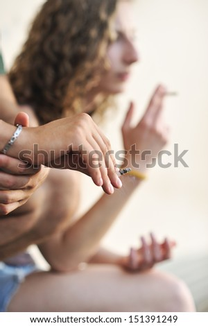 Cropped shot of two teenagers smoking cigarettes  - stock photo