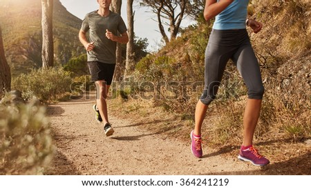 Cropped shot of two young people running on mountain trail.  Young man and women trail running on a mountain path. - stock photo