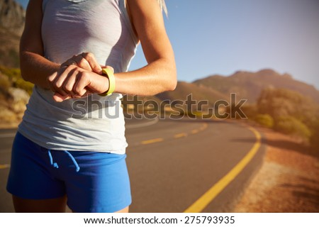 Cropped shot of woman checking her sports watch - stock photo