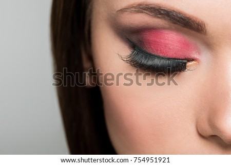 cropped shot of woman with false eyelashes and fashionable makeup isolated on grey