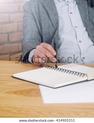 cropped shot of workspace with man's hands with pen and stuff on the desk