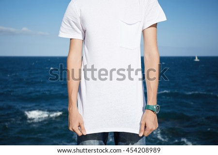 Cropped shot of young Caucasian man wearing jeans and blank white T-shirt with copy space for your promotional content, against blue sky and sea background. Advertising and T-shirt design concept - stock photo