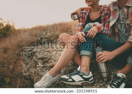 Cropped shot of young man and woman sitting on a stone with thermos. Teenagers loving couple wearing casual clothes relaxing outdoors - stock photo