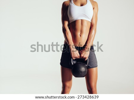 Cropped shot of young woman in sportswear holding a kettle bell. Strong fitness female exercising crossfit with kettlebell in studio. Female model with muscular and slim body on grey background. - stock photo