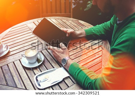 Cropped shot view of a smart male student reading news on digital tablet while breakfast in sidewalk cafe, man holding touch pad with copy space screen for your text message or promotional content - stock photo