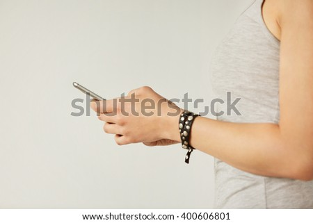 Cropped shot view of a woman's hands holding mobile phone, young female person chatting on cell telephone during work break. - stock photo