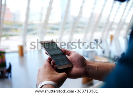 Cropped shot view of man's hands orders electronic ticket via mobile phone application during summer trip, young male reading text message on cell telephone while standing in waiting hall of airport - stock photo