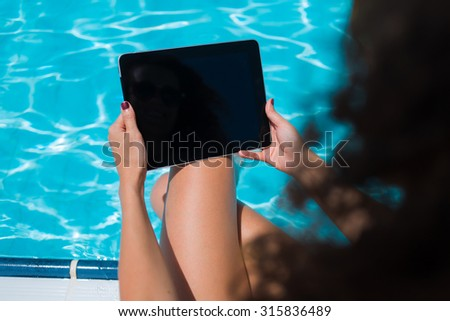 Cropped shot view of woman holding touch pad with blank copy space screen for your information content while sunbathing near pool, female freelancer using touch pad for remote work during vacations