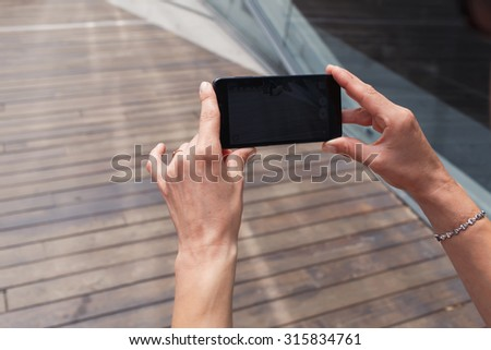 Cropped shot view of woman's hands holding mobile phone with copy space area for your text message or advertising content, female taking a picture with her smartphone camera in urban setting  - stock photo
