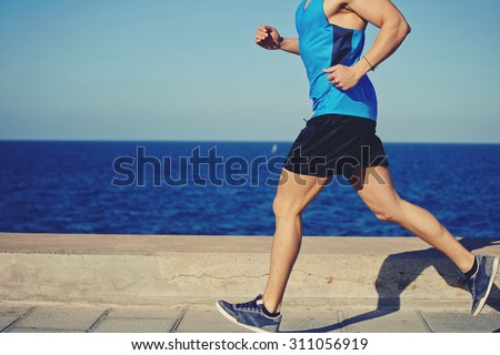 Cropped shot with muscular build man running along the seashore with copy space area for your text message or advertising content, male jogger working out outdoors o the beach at sunny afternoon - stock photo
