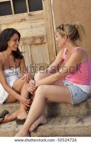 Cropped side view of two young women sitting on an outside porch and talking. They are smiling at each other. Vertical format. - stock photo