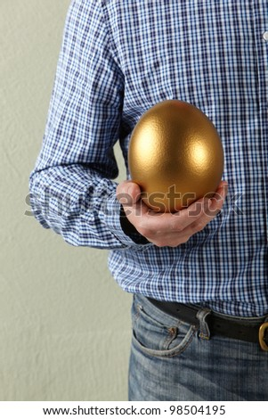 Cropped Studio Shot Of Man Holding Golden Egg - stock photo