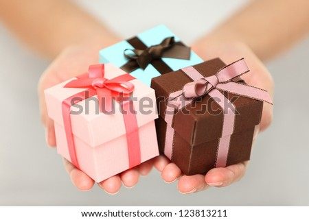 Cropped view image of a woman holding three colourful Christmas gifts with decorative ribbons and bows in the palms of her her hands, can also be used for anniversary, birthday or other celebration - stock photo