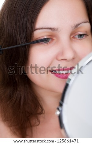Cropped view image of an attractive woman applying mascara to her eyelashes - stock photo
