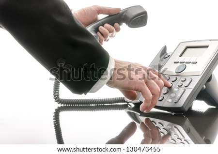 Cropped view of a business man dialing a phone number on a black table. - stock photo