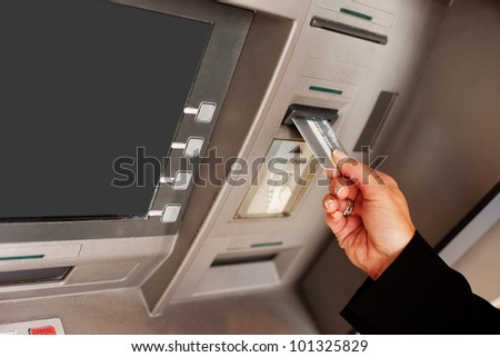 Cropped view of a female hand inserting a bank card into an ATM to begin a financial transaction