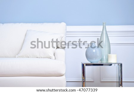 Cropped view of a living room, focusing on a white couch and side table with vases. Horizontal format.