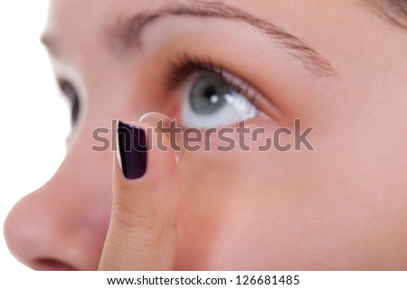 Cropped view of a woman inserting a contact lens into her eye looking upwards in preparation for placing the lens on the cornea - stock photo