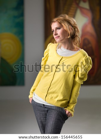 cropped view of beautiful woman with blonde hair standing and posing in an art gallery, while looking at an artwork displayed in front of her - stock photo