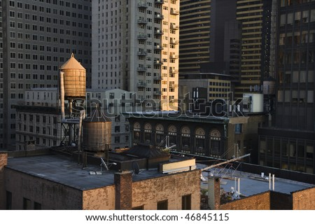 Cropped view of buildings in New York City and rooftop water towers. Horizontal shot.