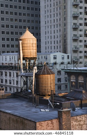 Cropped view of buildings in New York City and rooftop water towers. Vertical shot.
