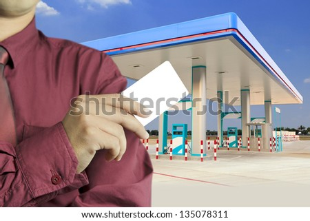 Cropped view of Businessman hand holding blank card in gas station - stock photo