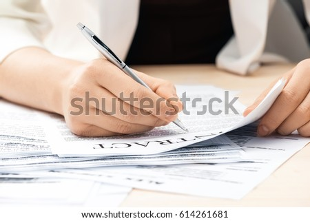 cropped view of businesswoman signing contract documents sitting at table