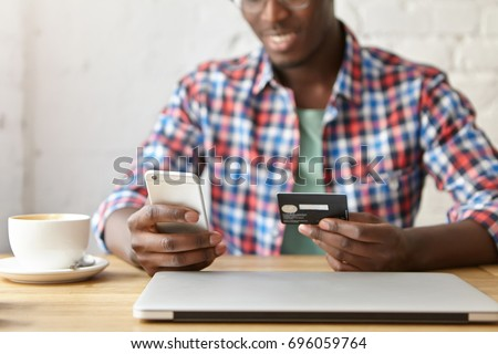 Cropped view of cheerful young African male in checkered shirt making transaction using mobile naming application on his smart phone, paying for lunch at restaurant. Selective focus on man's hands
