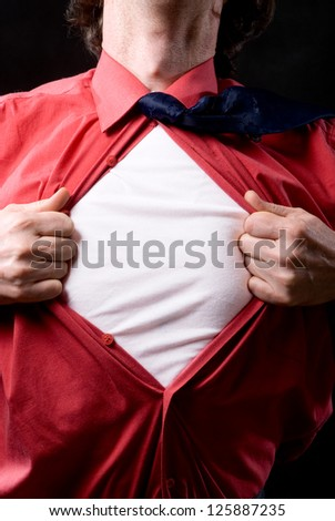 Cropped view of frustrated  man tearing off his shirt on black background - stock photo