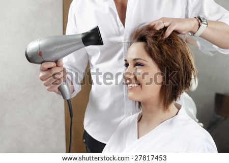 cropped view of hairstylist drying woman?s hair. Side view - stock photo