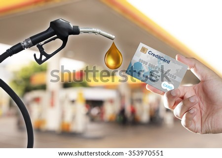 Cropped view of hand holding credit card in gas station - stock photo