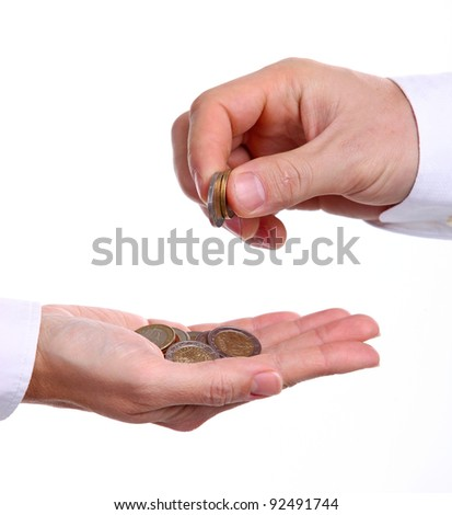 Cropped view of male hand giving euro coins to another person - stock photo